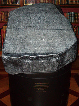 """Replica of the Rosetta Stone in the King's Library of the British Museum as it would have appeared to 19th century visitors, which was open to the air, held in a cradle that is at a slight angle from the horizontal and available to touch"""