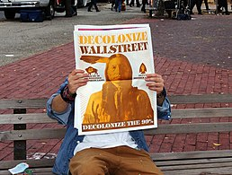"Occupier holding up newspaper, covering his face. Back of paper shows Native America, with caption ""Decolonize WallStreeet, Decolonize the 99%"""