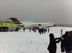 Delta Air Lines Flight 1086 - The MD-88 aircraft rests on the seawall after veering off the runway and skidding across the airfield for over a thousand feet, destroying approximately 940 feet of perimeter fence.