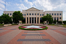 Front picture of a two-story administration building on a cloudy day. The walkway is shown leading up to the building including a circular garden in with white flowers forming a star.