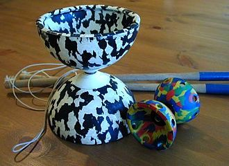 Diabolo - Large and miniature Western rubber diabolos. Wooden sticks are shown in the background.