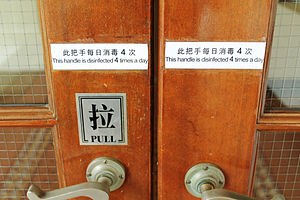 Disinfectant - Doors at the Hong Kong Museum of History with signage stating that the doors are disinfected frequently.