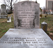 "A color photograph of a grave. The headstone reads Francis Scott Key Fitzgerald September 24, 1896 December 21, 1940 His Wife Zelda Sayre July 24, 1900 March 10, 1948. ""So we beat on boats against the current, borne back ceaselessly into the past"" – The Great Gatsby"