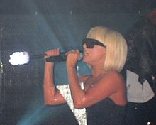 Upper torso of a blond woman in a bob cut looking to the right. She wears black sunglasses and holds a stick with a light atop it. The woman sings in a microphone on her left hand. A silvery triangular piece is visible on her dress.