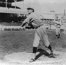 A man wearing a baseball uniform stands truned to his right having just pitched a baseball from the pitcher's mound.