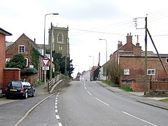 A narrow road up a slight incline between red brick buildings of a variety of styles and ages. The pavement on the left is raised above the roadway. Left on the skyline is the square greenish church tower.
