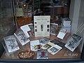 Fotografie cu vitrina librăriei Mihail Sadoveanu din București cu afișul de la lansarea cărții Între noi-timpul 115 poeme alături de celelalte cărți ale Adelei Popescu.jpg