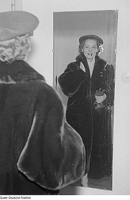 """Fotothek df roe-neg 0006507 014 Eine Frau posiert mit Mantel und Hut vor einem Spiegel bei der """"Internationalen"""