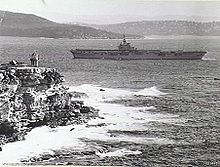 Grainy photograph of an aircraft carrier manoeuveing around a cliff-faced headland with a lighthouse on top. More landmasses are visible in the background.