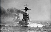 A large gray battleship steams in choppy seas; thick black smoke billows from its funnels. Two battleships are directly behind