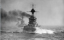 A row of three black battleships underway with smoke coming out of their funnels.