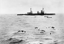 A large warship lowers boats to pick up sailors floating in the open water