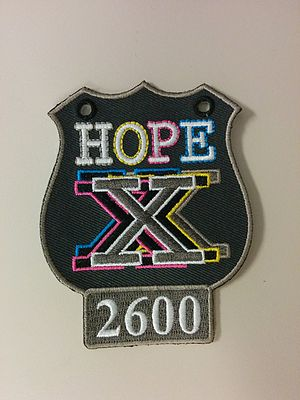 Hackers on Planet Earth - The badge used at HOPE X. It was a patch evocative of a police shield, with the 2600 logo prominent at the bottom.