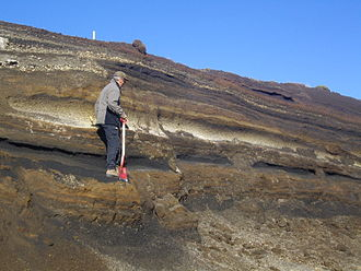 Geochronology - Tephra horizons in south-central Iceland. The thick and light-to-dark coloured layer at the height of the volcanologists hands is a marker horizon of rhyolitic-to-basaltic tephra from Hekla.