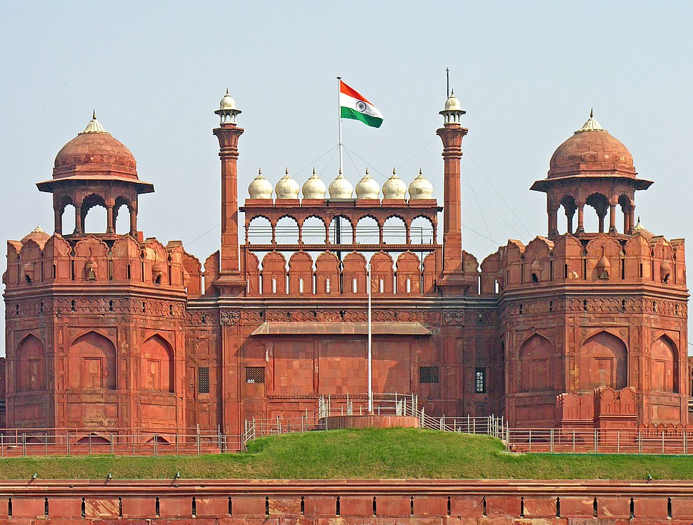 The national flag of India hoisted on a wall adorned with domes and minarets.