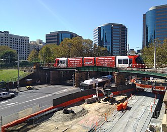 Light rail in Sydney - An Urbos 3 arrives at Central on the Inner West Light Rail with the CBD and South East Light Rail under construction below. The bridge was originally built for Sydney's former tram network.