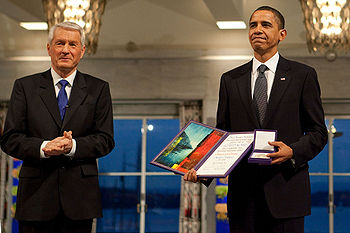 Barack Obama stands to the left of another man, both in dark suits, Obama holding his award.