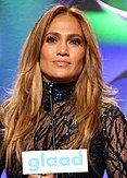 A portrait of Jennifer Lopez posing onstage in a black see-through outfit.