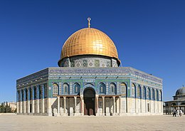 An octagonal, multi-colored building, the upper trim of which is inscribed in Arabic, topped by a golden-plated dome