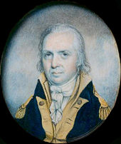 A man with stringy, gray hair wearing a navy jacket with gold epaulets and collar and a high-collared white shirt gathered at the neck