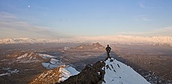 An ISAF member stands on top of a hill watching a snow-covered mountain range in Kabul province (March 1, 2013).