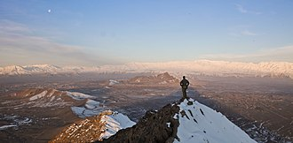 Kabul Province - An ISAF member stands on top of a hill watching a snow-covered mountain range in Kabul province (March 1, 2013).