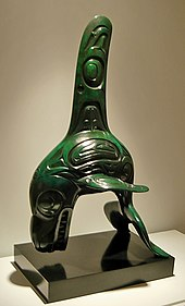 Jade carving of a killer whale with exaggerated fins and bared teeth. Its body and fins are engraved with nested ovals and other patterns.