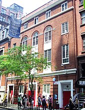 A red-brick three-story building with a tree outside it.