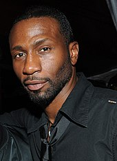 Face of an African-American male with short cropped beard and mustache. He is wearing a black shirt and shiny, black tie.