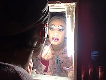 A drag queen putting on lip liner