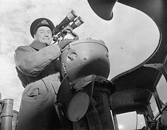 HMS Comet (H00) - Lieutenant-Commander Desmond W. Piers, Commanding Officer, on the bridge of the destroyer HMCS Restigouche, which is escorting convoy SC-107 at sea, 21 April 1944