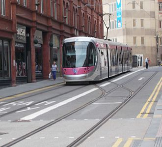 West Midlands Metro - In June 2016, shortly after the opening of the extension to Grand Central, a tram stands on the reversing spur in Stephenson Street. The extension to Centenary Square will continue  to the right behind the tram along Pinfold Street.