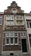 foto van Huis, met aan de straat een in- en uitgezwenkte top in de trant van Hans Vredeman de Vries boven een Maaslands hoofdgestel met consoles.