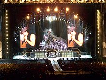 Distant shot of a concert stage. An arch with spotlights stands above a life-size locomotive and two big screens which display the male singer in left profile. Below and in front of the locomotive is musical equipment and four band members. At extreme left is a male playing guitar, he wears a school boy's uniform. Central stage has two guitarists with a drummer and his kit between them. Front stage has a catwalk with the singer turned to his left profile, he is cradling the microphone in his right hand and has his left fist near his face. He wears a cap, dark singlet and jeans.