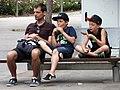 Man and Boys on Bench - Barcelona - Catalunya - Spain (14472591828).jpg