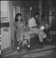 Manzanar Relocation Center, Manzanar, California. Evacuees waiting their turn to be called by the n . . . - NARA - 538150.tif