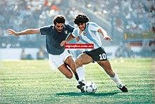 Photographie en couleurs. Un joueur italien, Gentile, à gauche avec son maillot bleu foncé, est aux prises avec un joueur argentin, Maradona, à droite avec son maillot rayé bleu ciel et blanc.