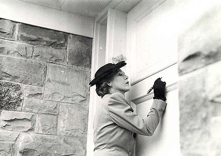 Mary Pickford War Funds bungalow, 1943 Mary Pickford signing the entrance to the Mary Pickford War Funds bungalow.jpg
