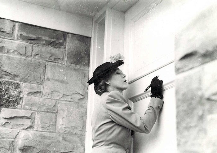 Mary Pickford signing the entrance to the Mary Pickford War Funds bungalow