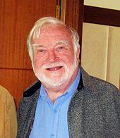 Photo en buste d'un homme âgé aux cheveux et à la barbe blanche