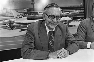 Max van der Stoel sits smiling at a table in an airport. Planes can be seen behind him.