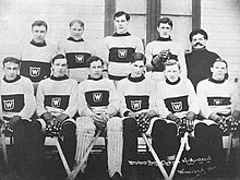 "Black and white image of eleven men posing for a photo, with six of them sitting on a bench, and the other five standing behind them. All but one man are wearing the same wool sweater, white with a dark band around the torso; within the band is a small white ""W"" surrounded by a white square. The men on the bench are clearly holding hockey sticks, and the man third from the left is wearing padding on his legs. The man not wearing a sweater, standing on the far right, is simply wearing a dark shirt."