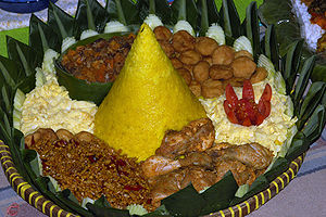 Javanese cuisine - Tumpeng cone shaped rice surrounded with chicken, omelette eggs, sambel goreng ati (beef liver in sambal), potato perkedel, and tempeh orek.