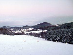 Nerother Kopf an einem späten Winternachmittag von Westen her; am Fuß des Berges in der linken Bildmitte der namengebende Ort Neroth; die Ruine Freudenkoppe bleibt unter Buchen verborgen.
