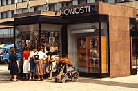 Newspaper stall and women in East Berlin, with person in wheelchair, 1984.jpg