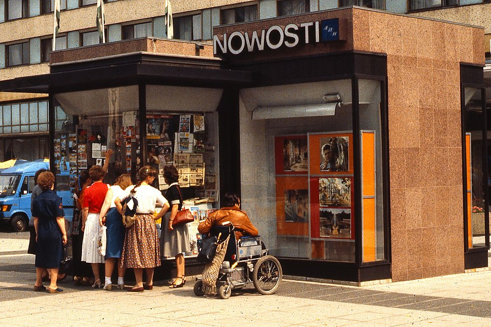 Newspaper stall and women in East Berlin, with person in wheelchair, 1984