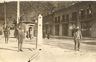 Battle of Ambos Nogales - American and Mexican soldiers guarding International Street in Ambos Nogales. The obelisk in the center is a border marker, which still stands. A Mexican border post is in the middle foreground of the image. The Americans had a similar one on their side.