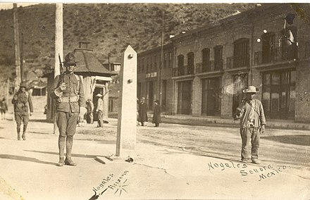An American and Mexican soldiers guarding the border in Ambos Nogales during the Mexican Revolution. The city was the site of two separate engagements in the Border War, a series of military engagements along the border during the Revolution. Nogales Arizona 1910-1920.jpg