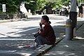Old woman sitting and smoking in front of Maruyama park, Kyoto (円山公園) - panoramio.jpg