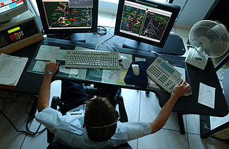 Automatic identification system - A U.S. Coast Guard Operations Specialist using AIS and radar to manage vessel traffic.